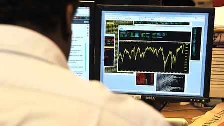 An office worker views a graph showing today's movement in the FTSE 100 Index which has climbed abov