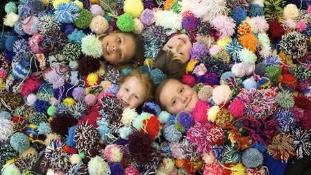 Pupils of Manor Road Infants and Junior school with 1400 of the 10,000 pom poms they've knitted to r