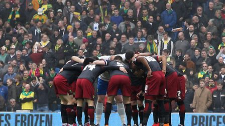 The Norwich City players in the pre-match huddle in front of their fans before the game at Brighton.