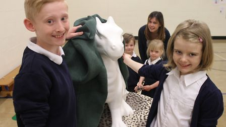 Holt Primary School pupils Mackenzie, 10, and Daisy, 9, unveil a ready-to-paint Go Go Dragon, watche