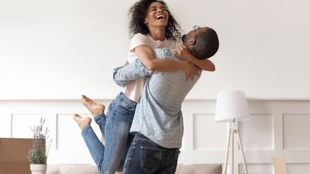 African husband lifting happy wife laughing celebrating moving day with boxes, excited first time ho