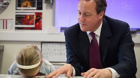 Prime Minister David Cameron helps with a reading lesson at the Sacred Heart Roman Catholic Primary