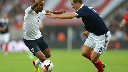 Norwich City's Steven Whiitaker gets to grips with England's Theo Walcott while on duty for Scotland