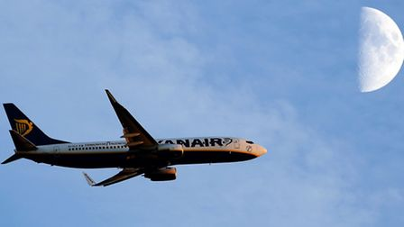 Ryanair passenger plane as it passes the moon after take off from Stansted Airport in Essex: Chris R