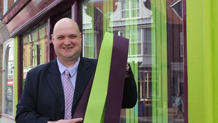 Insurance broker Andrew Cunningham-Brown outside his purple and green office in Church Street. Pictu
