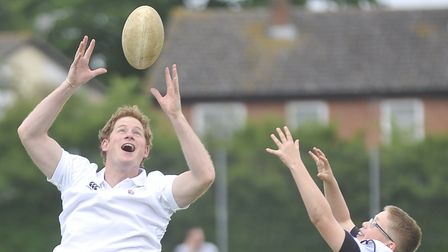 Prince Harry goes to catch a rugby ball while playing the game with kids at Inspire Suffolk during h