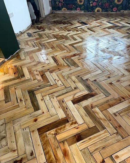 The incredibleherringbone flooring using all recycled wooden pallets.