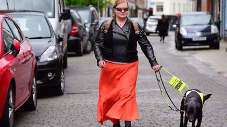 Mhairi Claxton and her guide dog Bramble are forced to walk in the road due to parked cars on the pa