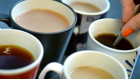 A woman stirs cups of tea and coffee, London PRESS ASSOCIATION Photo. Anthony Devlin/PA wire