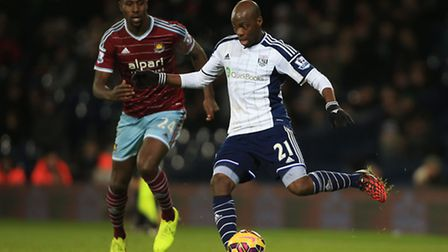 West Bromwich Albion's Youssuf Mulumbu holds off a challenge from West Ham United's Carlton Cole dur