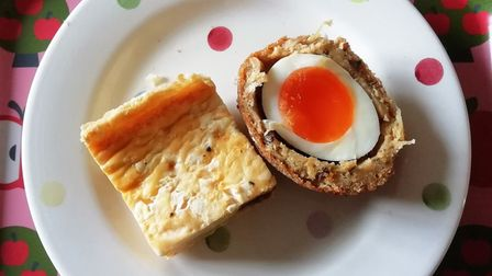 Quiche and vegetarian Scotch egg on a spotty plate