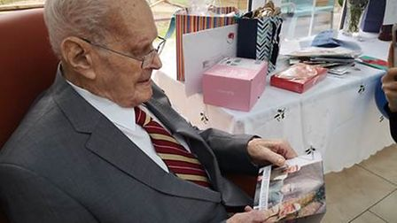 Wilfred Goddard looks over photos and cards sent for his 103rd birthday