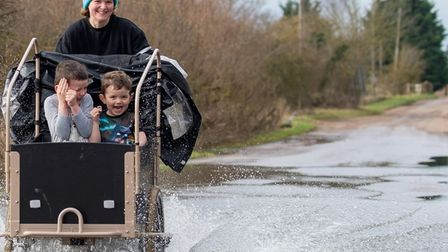 Sally and her sons Fin and Sam cycling through Sutton in - they weren't letting a flooded road stop them Bicycle Sun behind cloud