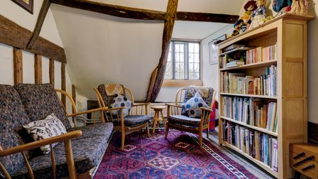 Photograph showing the interior of a large medieval cottage with a sloping ceiling, exposed timbers and a bookshelf full...
