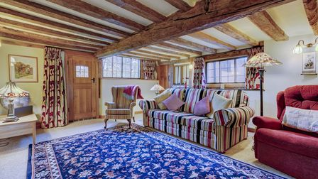 Photograph showing the inside of a large reception room with exposed timber beams on the ceiling, a stripe classic-shaped...