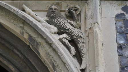 A carving of the entrance to Peasenhall church of a fur covered man, known as a woodwose