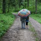 two children under a brightly coloured umbrella on a country road in the rain