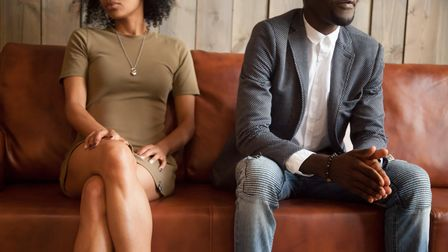 Unhappy couple sitting on couch after quarrel fight thinking of break up or divorce