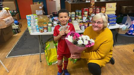 Five-year-old Cole Casey with Sharon Thompson at the Pine Close Community Centre. Cole donated around £200 worth of food and gave the leftover money to Ms Thompson - who helps to feed Thetford's vulnerable.