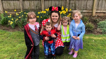 The children and nursery manager Emily surrounded by daffodils in the Hub garden.