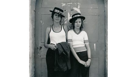 Two people pose for the camera wearing hats in front of a doorway
