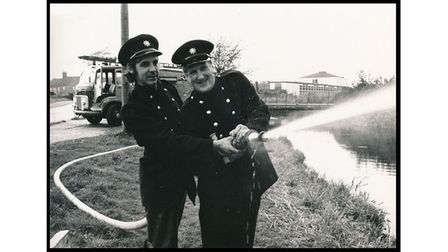two firefighters playing with a hose