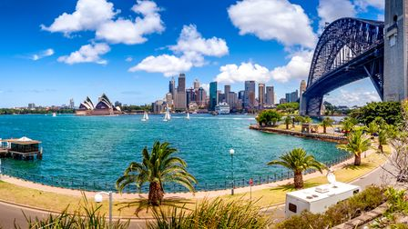 View of Sydney skyline as seen from across the Sydney Harbour Bridge in the right side of the image.