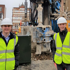 Two apprentices in high vis vests and helmets on a building site