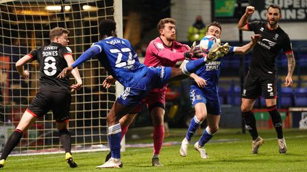 Lincoln City keeperAlex Palmer saves as Toto Nsiala stretches for the ball.