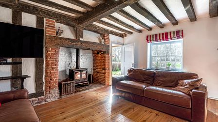 Photograph showing a living room with a large leather sofa, brick-built hearth and timbered ceiling