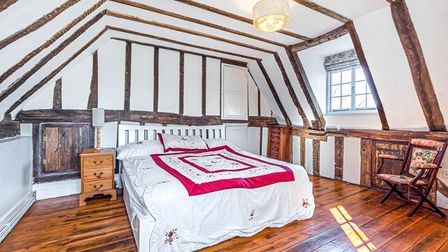 Photograph showing a large double bedroom with a sloping ceiling, wooden floors and timber detailing