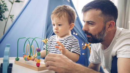 Father and baby son playing on floor in front of tent with toys, they spending time in isolation tog