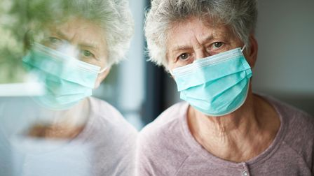 a old woman or grandma is wearing a respirator or surgical mask and is looking out the window while