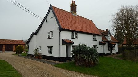 Photograph showing the exterior of a pretty white cottage with a tiled roof and chimney and a shingle driveway leading up...