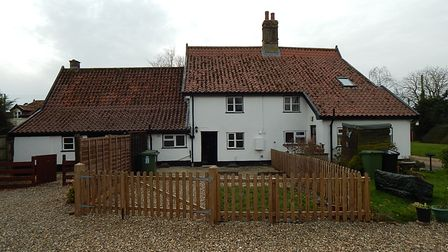 Photograph showing the exterior of a substantial white cottage enclosed with timber fencing
