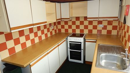 Photograph showing the inside of a retro cottage kitchen with red and white tiles, white cupboards and a cooker