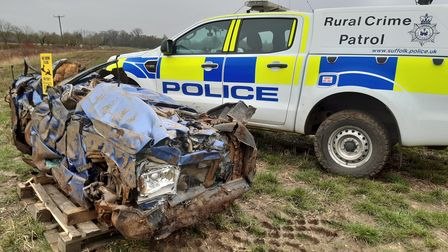 A crushed car with a police rural crime vehicle in Suffolk