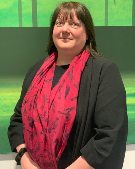 Woman in red scarf standing in front of green background