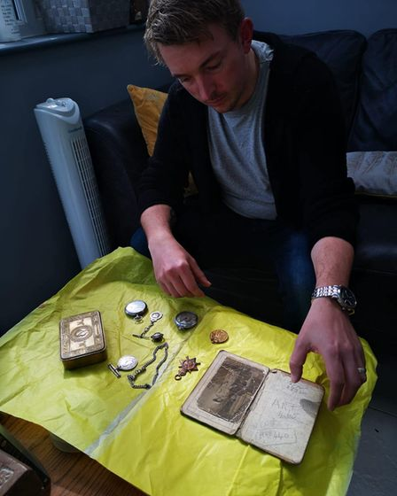 Adam Simpson-York looking through the items he has inherited from his great-grandfather.