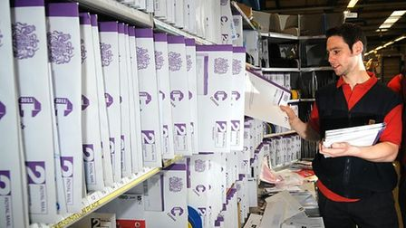 Postman Laurence Bury sorting Census forms ready for delivery in 2011