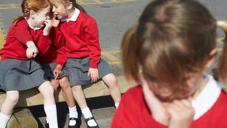Female Elementary School Pupils Whispering In Playground About Another Pupil