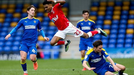 Charlton Athletic's Ian Maatsen (centre) after being challenged by AFC Wimbledon's George Dobson (ri