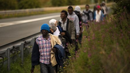 Migrants walk next to a road as they try to access train tracks which lead to the Channel Tunnel, in