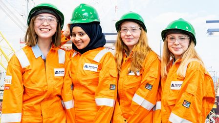 A picture of four female students in orange overalls and green hard hats working in the energy sector