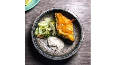 A dish of savoury baklava with a dip and salad
