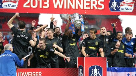 File photo date 11/5/2013 of Wigan Athletic players celebrate their victory with the FA Cup trophy,