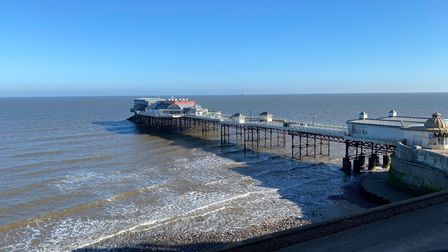 Photograph showing Cromer Pier and the shore line under bright blue sky