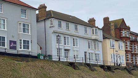 Photograph showing a row of pastel coloured terraces in need of renovation above a seaside promenade