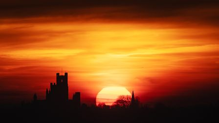 The sun rises behind Ely Cathedral in The Fens.