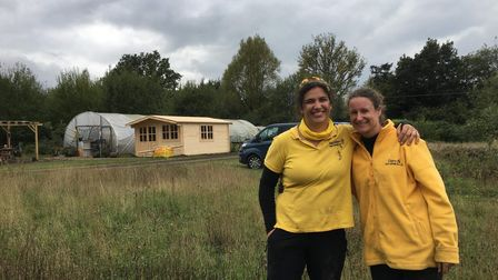 Steph Holland and Claire Unwin in front of the newly built log cabin at The Hive, October 2020